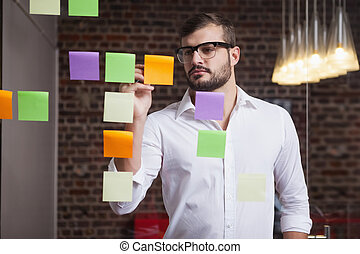 Casual businessman writing on sticky notes