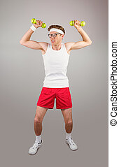 Geeky hipster posing in sportswear with dumbbells on grey...