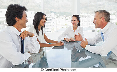 Happy business team talking together while at work