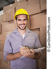 Worker with clipboard in warehouse
