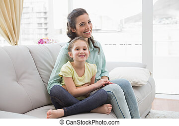 Cute mother and daughter on the couch