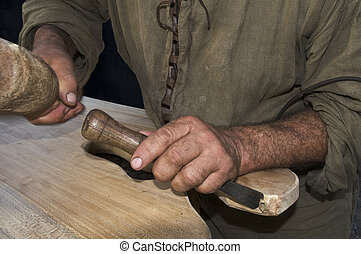 Wood carving - Craftsman hands with tool carving a wood...