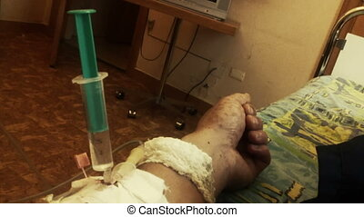 Hand of sick person with syringe and drip - Close-up shot of...