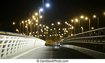 Empty bridge at night with lights and cars
