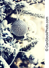 Christmas ball on snow covered fir tree in silver tone