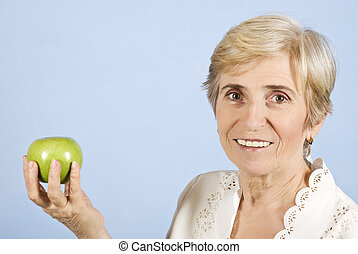Senior woman holding and apple