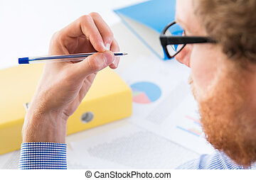 Man holding a pen with his left hand - office