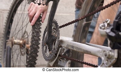 Mechanical Inspection on a Bicycle - Man spins the pedals by...