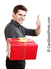 Holiday Man giving red gift box showing thumb up - Holiday...
