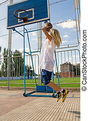Girl playing basketball outside - Young blond girl is...