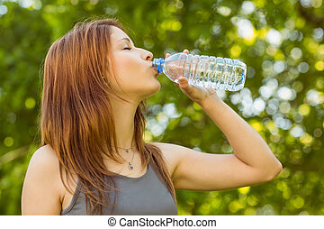 Pretty redhead drinking water in park at sunshine