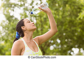 Pretty brunette pouring water over herself in the park