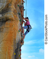 Active teen girl climbing artificial rock - Active alpinist...