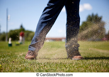 Golf Swing - A golf swing on a driving range with sand in...