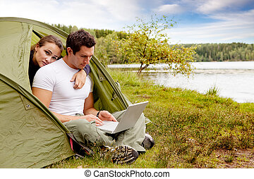 Remote Office - A couple looking at a computer while camping...