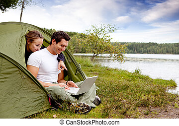 Camping Computer - A couple looking at a computer while...
