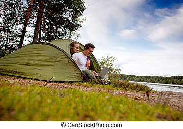 Computer Outdoor Tent - A man and woman using a computer...