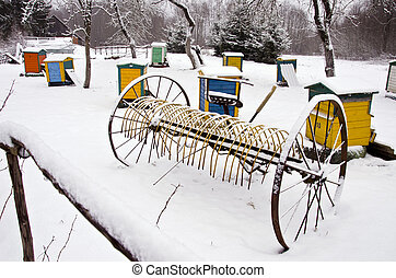 Old snowy horse drawn hay rake and beehive in winter farm...