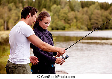 Teach Fishing - A man showing a woman how to fish