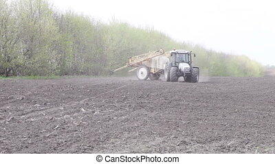 tractor with sprayer travels on the road - tractor with...