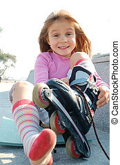 child putting on her rollerblade skate - adorable little...