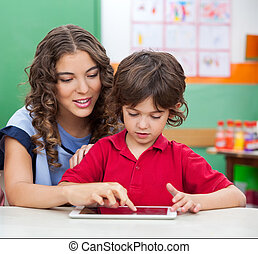 Teacher Teaching Students To Use Digital Tablet - Young...