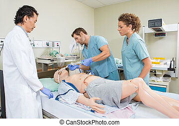 Nurse Adjusting Endotracheal Tube On Dummy Patient - Male...