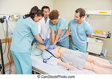 Medical Team Performing CPR On Dummy Patient - Doctor and...