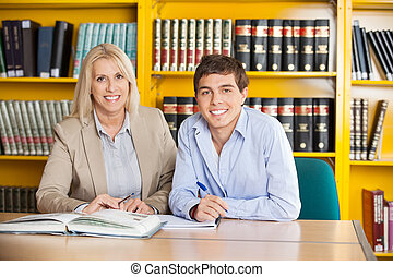 Student And Teacher With Books Sitting At Table In Library -...