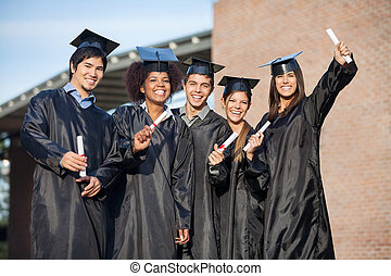 Students In Graduation Gowns Holding Diplomas On University...