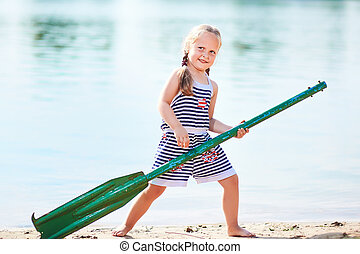 happy girl with paddle at beach
