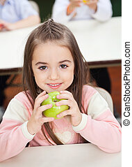 Girl Holding Smith Apple With Classmates In Background -...