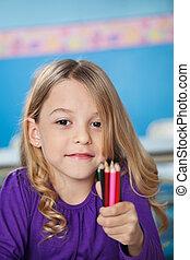 Girl Holding Bunch Of Color Pencils In Preschool