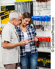 Father And Daughter Looking At Wrench In Shop - Senior man...