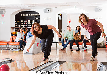 Man And Woman Playing in Bowling Alley - Young man and woman...