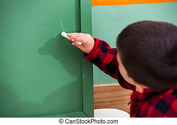 Boy Writing On Green Chalkboard In Preschool - Little boy...