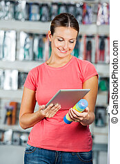 Woman Scanning Product Through Digital Tablet In Hardware...