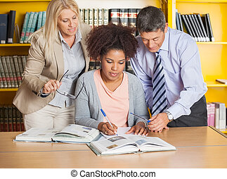 Student Writing In Book While Teachers Assisting Her At Library