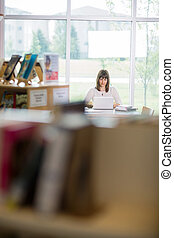 Student Using Laptop In Library - Female university student...