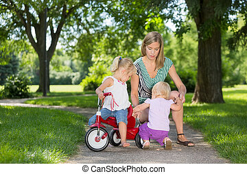 Mother And Children With Tricycle In Park - Mother and...