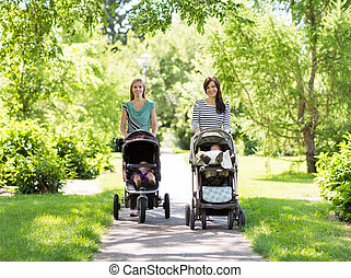 Mothers With Baby Strollers Walking In Park - Portrait of...