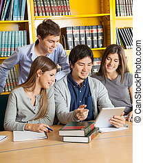 Students With Digital Tablet Discussing In College Library -...
