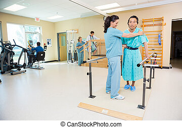 Therapists Assisting Patients In Hospital Gym - Female...