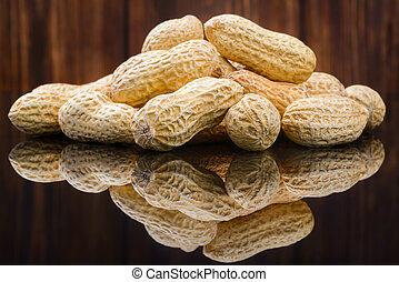 Many peanuts in shells, one upon the other on wood...