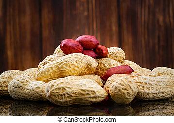 Peeled peanut on well peanuts on wooden background