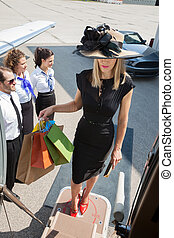 Woman Carrying Shopping Bags While Boarding Private Jet -...