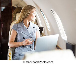 Businesswoman Looking Through Window Of Private Jet - Mid...