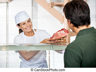 Butcher Selling Fresh Meat To Customer - Happy mature female...