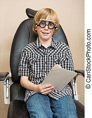Boy With Trial Frame Holding Test Chart At Optician