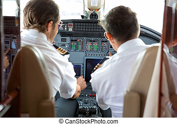Pilots Operating Controls Of Corporate Jet - Rear view of...